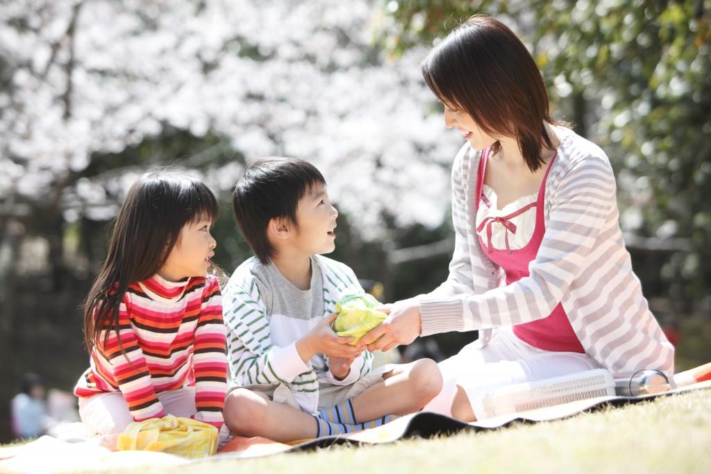 日差しの中でピクニックを楽しむ親子