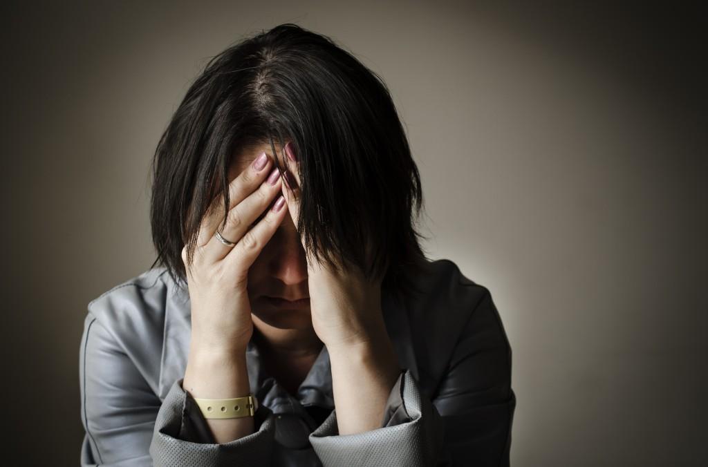 心労に頭を抱えて苦悩する女性