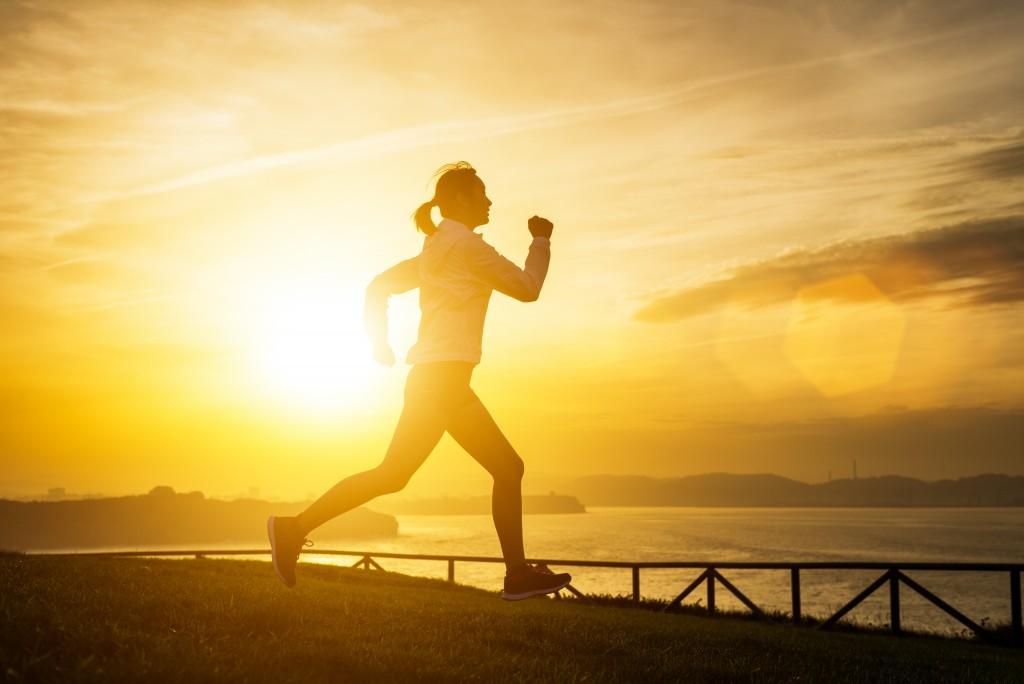 太陽の光を浴びて走る女性